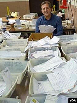"""Pete Fontana, pengawas """"Operasi Sinterklas"""" berada di antara tumpukan surat untuk Sinterklas."""