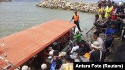 Nhân viên cứu hộ, cảnh sát và người dân chuẩn bị đưa thi thể một nạn nhân lên bờ ở Kolaka, đông nam đảo Sulawesi, Indonesia, ngày 20 tháng 12, 2015.