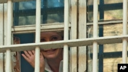 Former Ukrainian Prime Minister Yulia Tymoshenko waves from a prison window in Kyiv, Nov. 4, 2011.
