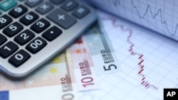 Euro banknotes and a calculator are placed on a currency graph and ticker (File)