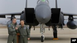 有关美国空军B-52轰炸机飞行任务的新闻发布会结束后,驻韩美军中将奥肖内西和韩国空军将领李莞根在一架韩国F-15战机前合影。
