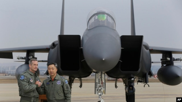 Lt. Gen. Terrence O'Shaughnessy, left, 7th Air Force commander of the U.S. Forces to Korea, and South Korean Air Forces Commander Lee Wang-geun pose in front of a South Korean F-15K fighter jet after a press briefing on the flight by a U.S. Air Force B-52
