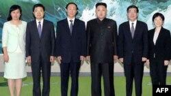 ຜູ້ນໍາເກົາຫຼີເໜືອ ທ່ານ Kim Jong Un (ທີ3 ຈາກຂວາ) ຖ່າຍຮູບຮ່ວມກັບທ່ານ Wang Jiarui (ທີ 3 ຈາກຊ້າຍ) ຫົວໜ້າກົມພົວພັນຕ່າງປະເທດຂອງພັກຄອມມີວນິສຈີນ ແລະ ພວກເຈົ້າໜ້າທີ່ອື່ນໆ ໃນວັນພະຫັດ ທີ 3 ສິງຫາ, 2012 ທີ່ນະຄອນພຽງຢາງ