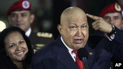 Venezuela's President Hugo Chavez points at his head to show that his hair has started to grow back after his last round of chemotherapy at Miraflores presidential palace in Caracas, Venezuela, October 11, 2011.