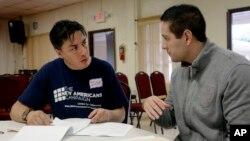 Iván Parra (izquierda), de Florida Immigrant Coalition, ayuda a Eduardo Feitosa, de 33 años, originario de Brasil, a presentar sus documentos para solicitar la ciudadanía estadounidense.
