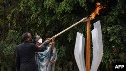 Le président rwandais Paul Kagame et la première dame Jeannette Kagame allument une flamme commémorative pour la 27e commémoration du génocide de 1994 contre les Tutsi au Mémorial du génocide de Kigali, au Rwanda, le 7 avril 2021.