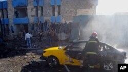 伊拉克基尔库克发生汽车炸弹袭击后,消防队员在现场灭火。(2014年1月7日)