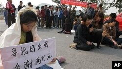 Relative of hit-and-run victim holds sign offering reward to witnesses at the site of the accident in Beijing, Oct. 18, 2006 (file photo).