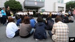 Các thành viên gia đình của hành khách trên chiếc phà bị chìm Sewol ngồi chờ gặp các thành viên phi hành đoàn trước tòa án ở Gwangju.