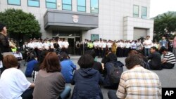 Para anggota keluarga korban tenggelamnya kapal feri Sewol mengikuti jalannya sidang peradilan awak kapal tersebut dari luar gedung pengadilan distrik Gwangju, Korea Selatan (10/6).