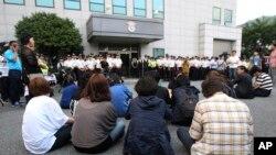 Para keluarga korban kapal Sewol yang tenggelam duduk di depan pengadilan distrik Gwangju di Korea Selatan (10/6). (AP/Ahn Young-joon)