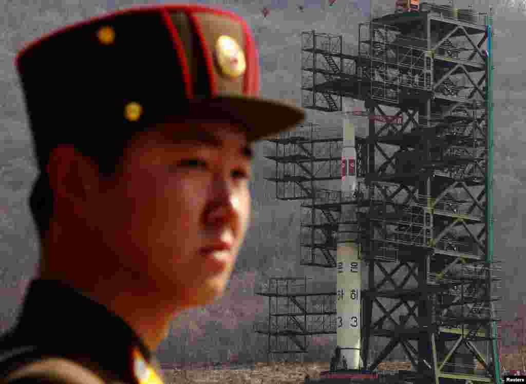 April 8: A soldier stands guard in front of the Unha-3 rocket sitting on a launch pad at the West Sea Satellite Launch Site, northwest of Pyongyang, North Korea.