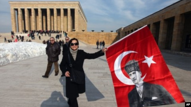 People hold national flags with posters of the founder of modern Turkey Kemal Ataturk as they visit his mausoleum in Ankara, Turkey, February 5, 2012.