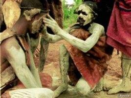 An Ogiek paints his fellow warrior's face