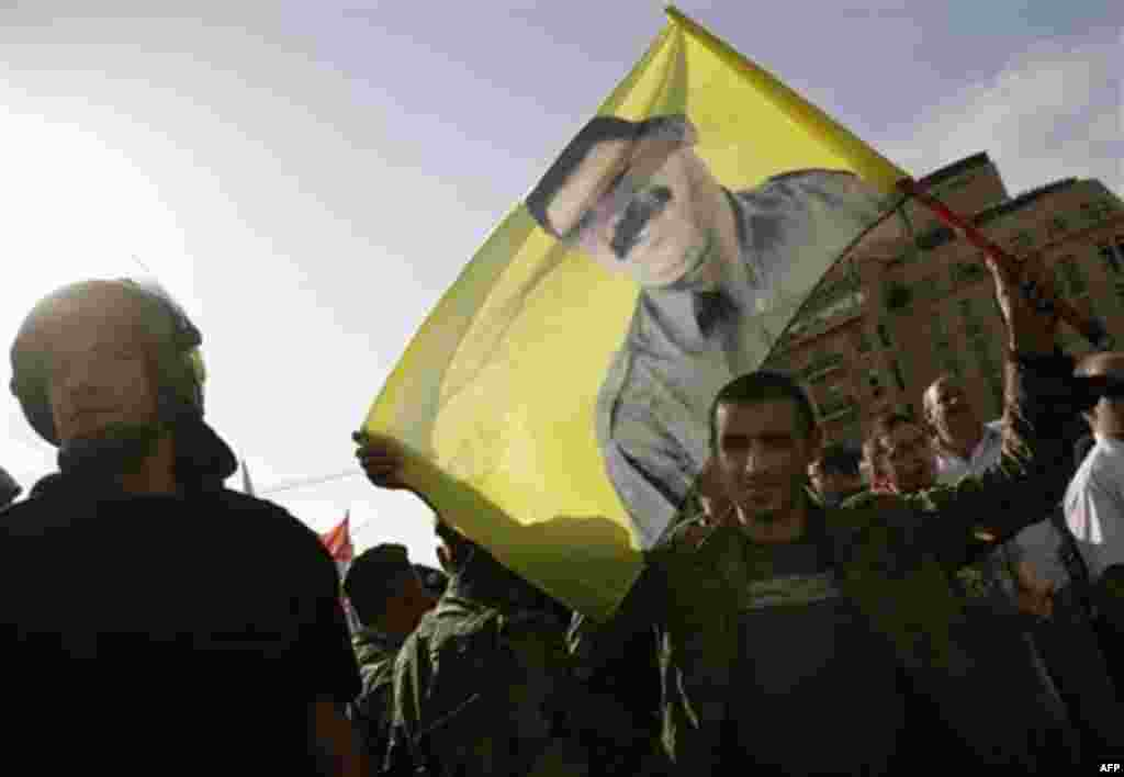 A Lebanese Kurdish man carries a flag bearing the picture of Kurdish rebel chief Abdullah Ocalan during a protest against the visit of Turkish Prime Minister Recep Tayyip Erdogan, in Beirut's Martyrs' Square, Lebanon, Thursday, Nov. 25, 2010. (AP Photo/G