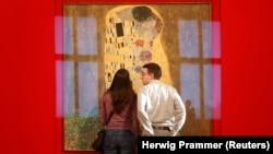 یک زوج در مقابل تابلوی بوسه اثری از گوستاو کلیمت