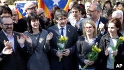 FILE - Former Catalan leader Carles Puigdemont, center, holds a bunch of flowers as he and supporters sing after a news conference in Berlin, Germany, Saturday, April 7, 2018.