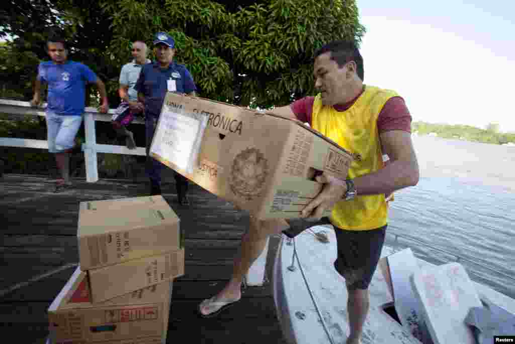 An election official carries a box of electronic ballots from a boat to a community on Ilha Grande island across the Amazon River from Belem, Oct. 5, 2014.