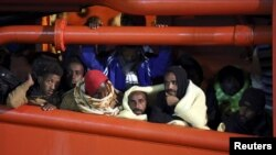 Migrants wait to disembark from a tug boat in the Sicilian harbor of Pozzallo, southern Italy, May 4, 2015.