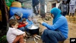 یک پناهجوی سوری و فرزندان او در حال تهیه غذا در یک اردوگاه پناهجویان در نزدیکی مرز سوریه و لبنان - آرشیو