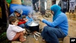 Anak-anak pengungsi Suriah dan ibunya sedang mempersiapkan makanan dekat tenda mereka di kamp pengungsi Ketermaya, Lebanon.(AP/Mohammed Zaatari)