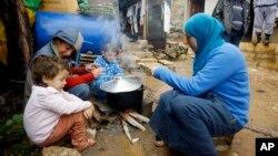 Bà mẹ và các con nấu ăn cạnh lều trong trại của người tị nạn Syria