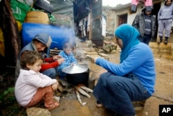 FILE - A Syrian refugee woman with her children prepares food near her tent in a camp for Syrians who fled their country's civil war, in the Chouf mountain town of Ketermaya, Lebanon.