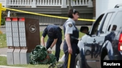 Police continue to search for evidence after a shooting in a residential neighborhood of the eastern city of Moncton, New Brunswick, June 5, 2014.