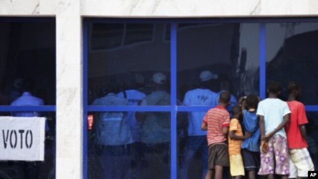 Boys watch electoral officials count votes through a window in Guinea's capital Bissau, March 18, 2012.