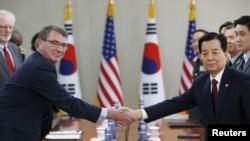 Menteri Luar Negeri AS Ash Carter (kiri) berjabat tangan dengan mitranya dari Korea Selatan, Han Min-koo, dalam pertemuan di Seoul, 10 April 2015.