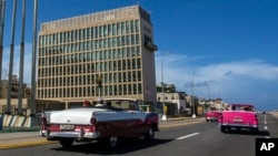In this Oct. 3, 2017, file photo, tourists ride classic convertible cars on the Malecon beside the United States Embassy in Havana, Cuba. T