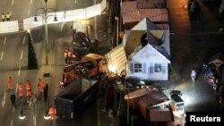 Para pekerja membersihkan lokasi serangan maut di pasar Natal di Berlin, Jerman (21/12). (Reuters/Christian Mang)