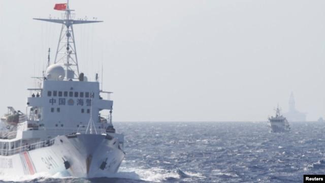 Tàu Cảnh sát biển Trung Quốc gần giàn khoan Hải Dương 981 ở Biển Ðông, khoảng 210 km (130 dặm) ngoài khơi bờ biển Việt Nam, ngày 14/5/2014. Trung Quốc cung cấp cho giàn khoan đầu một đoàn hộ tống gồm 80 tàu dân sự và tuần duyên đến địa điểm nằm trong vùng đặc quyền kinh tế của Việt Nam.