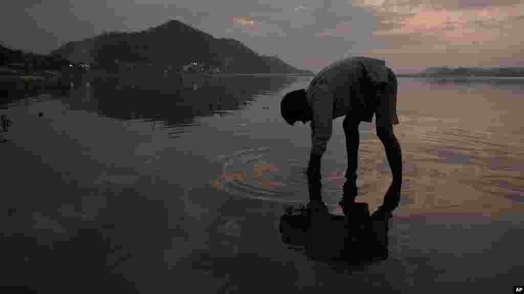 Un garçon cherche des pièces dans la rivière de Brahmaputra à la veille de la Journée mondiale de l'eau à Gauhati, en Inde, le 21 mars 2017.