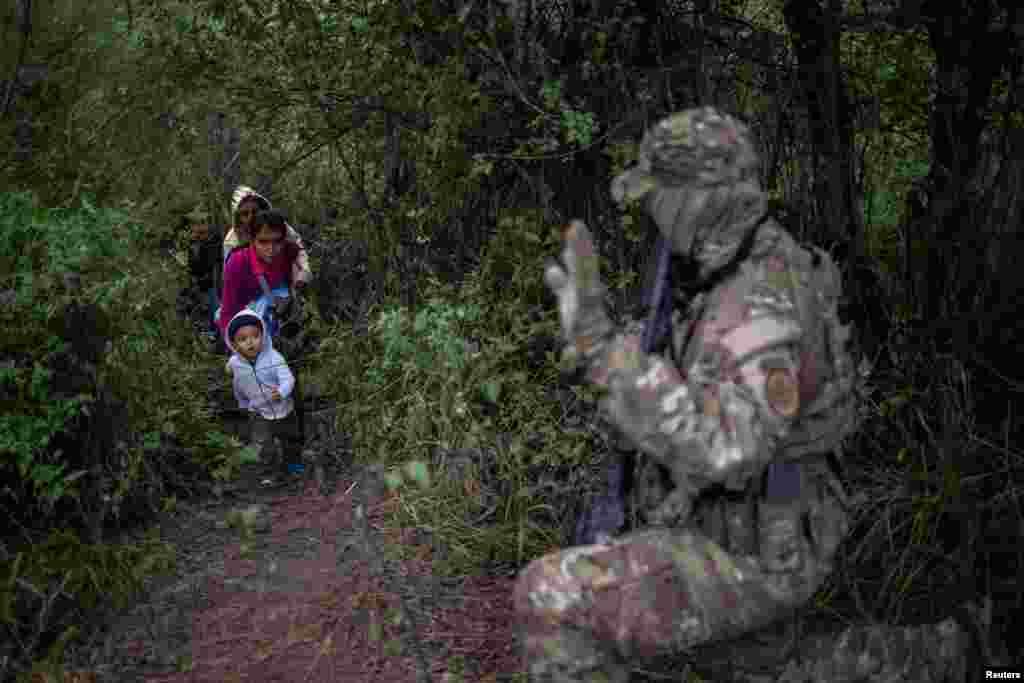 미국 텍사스주 프론톤에서 미국 국경수비 전술부대 소속 대원이 리오그란데 강을 건너 멕시코에서 미국으로 밀입국한 가족에게 신호를 보내고 있다.