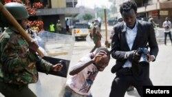 A Kenyan policeman beats a protester during clashes in Nairobi, May 16, 2016.