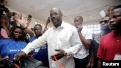 FILE - George Weah, former soccer player and presidential candidate of Congress for Democratic Change (CDC), votes at a polling station in Monrovia, Liberia.