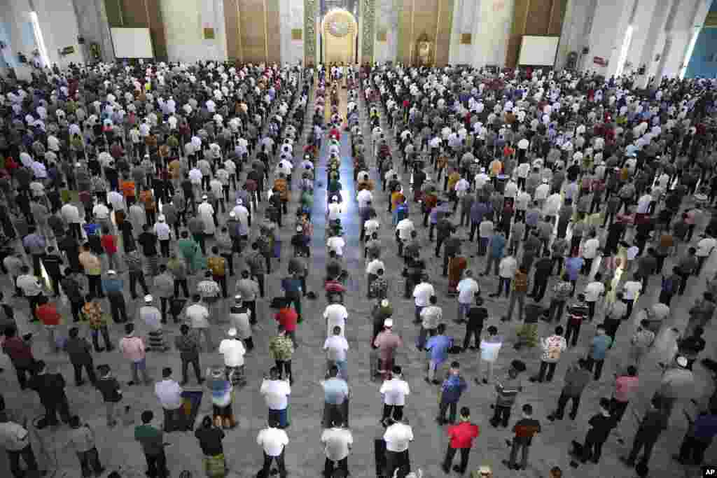 Muslim men perform Friday prayer at a distance of about one meter to each other as part of a social distancing effort to prevent the spread of new coronavirus outbreak, at Al Akbar mosque in Surabaya, East Java, Indonesia.