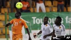 Emmanuel Eboue, da Costa do Marfim, perseguido por Miguel Geraldo Quiami e Dani Massunguna, durante o jogo que ditou a saída das Palancas Negras do CAN 2012