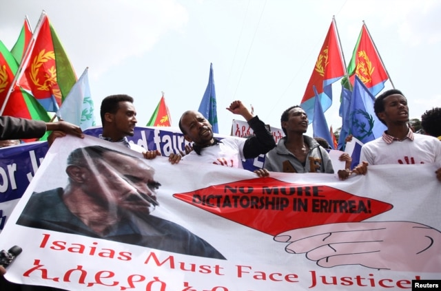 Eritrean refugees chant slogans as they hold a banner with the picture of President Isaias Afwerki during a demonstration in support of a U.N. human rights report accusing Eritrean leaders of crimes against humanity, in Ethiopia's capital, Addis Ababa, Ju