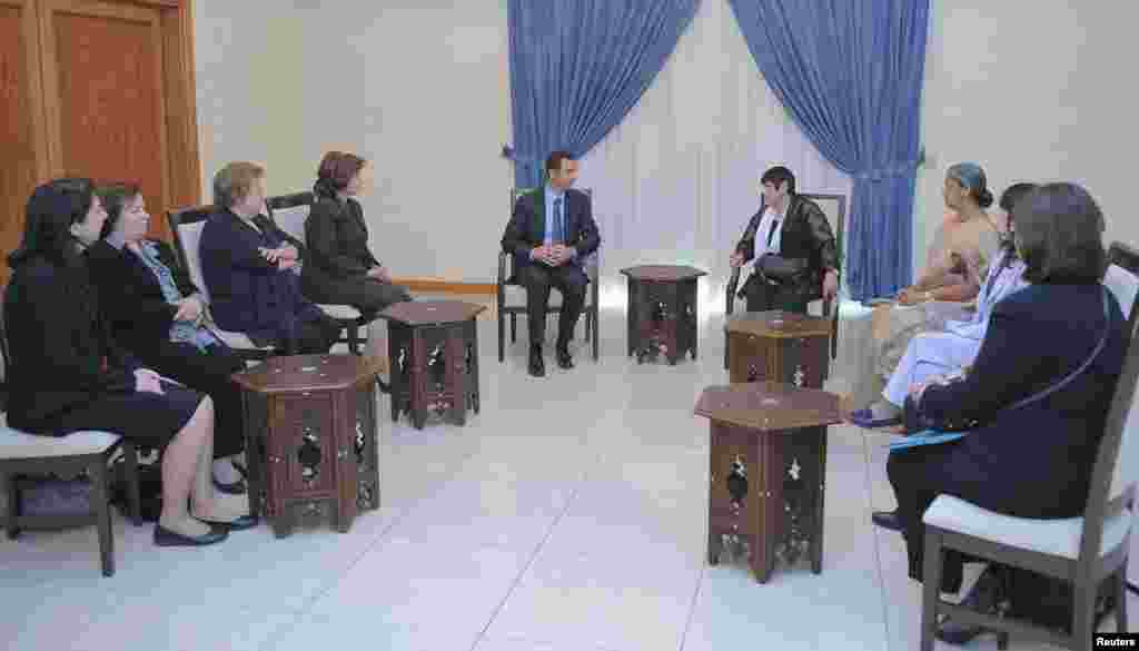 Syria's President Bashar al-Assad meets with a Women's International Democratic Federation delegation, headed by Marcia Campos in Damascus, Oct. 21, 2013. (SANA)