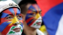 Activists with the colors of the Tibetan flag painted on their faces are seen at a rally in Taipei March 10, 2013.