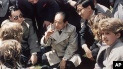 历史照片:中国共产党领导人胡耀邦在英国莎士比亚的出生地同英国女学生坐在草地上交谈。(1986年6月10日)
