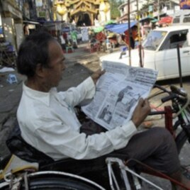 A Burmese man reads a newspaper reporting on the elections as he waits for trishaw passengers.