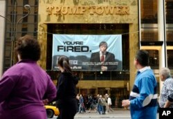 "In this Saturday, March 27, 2004 file photo, passersby look at a sign advertising the reality television show, ""The Apprentice,"" displayed at the entrance to the Trump Tower building in New York."