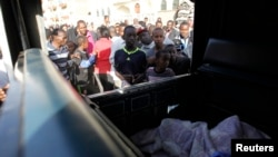 Residents jostle to see the slain body of a man inside a police pick-up truck near the scene of an explosion along Juja Road in the Kenyan capital Nairobi, March 31, 2014.