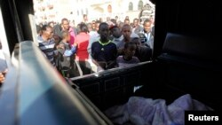 Warga berkerumun untuk melihat korban serangan bom di Jalan Juja, Nairobi, Kenya (31/3).