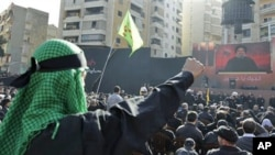 Lebanese Hezbollah supporters, raise their fists as they listen to Hezbollah's leader Sheik Hassan Nasrallah speak, on a giant screen, during Ashura day, in the suburbs of Beirut, 16 Dec 2010