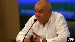 FILE - Dmitry Kiselyov, head of the official Russian state news agency Rossiya Segodnya, gestures during a press conference in Moscow on May 26, 2014.