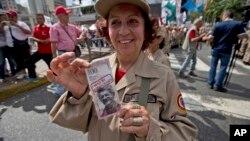 Una miembro de la milicia chavista muestra un billete de muestra con la imagen del presidente de la Asamblea Nacional, el opositor Henry Ramos Allup, durante una marcha de apoyo a gobierno.